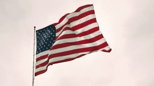 Flag of the United States of America on stormy gray background