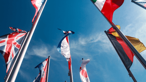 Upward view of flags against blue sky