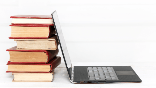 Laptop back-to-back with stack of red books, against white background