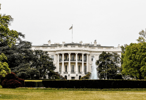 White house with columns and topped with flag
