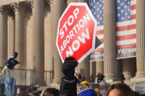 Stop sign saying Stop Abortion Now at a protest