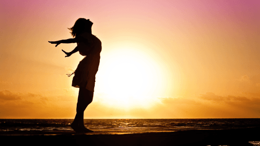 Silhouette of woman in front of water with sunset in bakcground
