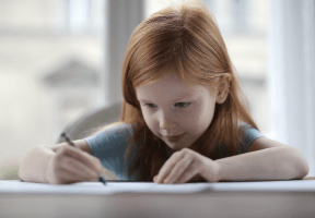 Young red-haired girl writing on paper at desk