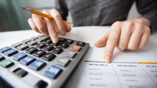 Close up of accountant doing taxes on a calculator