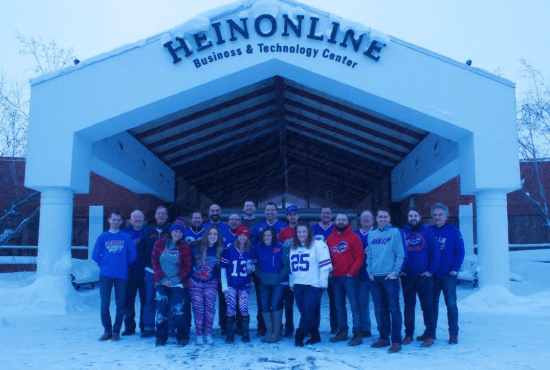 Group of HeinOnline employees in front of building in snow