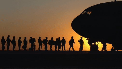 Silhouette of military personnel and plane