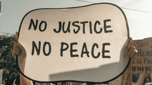 """Protestor holding """"No Justice, No Peace"""" sign"""