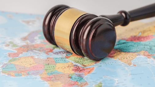 Brown gavel laying across colorful world map